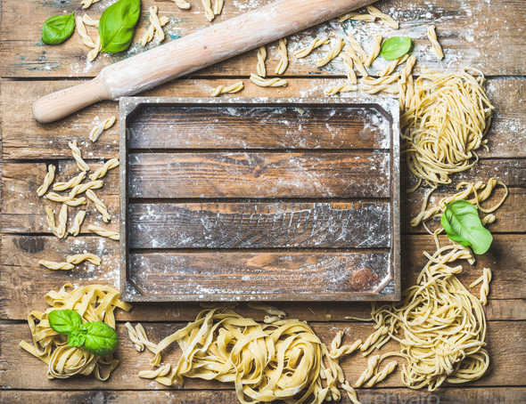 Various homemade uncooked Italian pasta and wooden tray in center - Stock Photo - Images