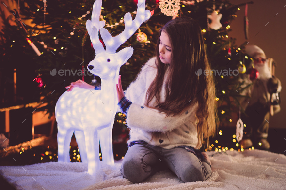 Little girl under Christmas tree at home - Stock Photo - Images