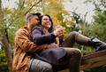Couple sitting on wooden bridge in autumn park