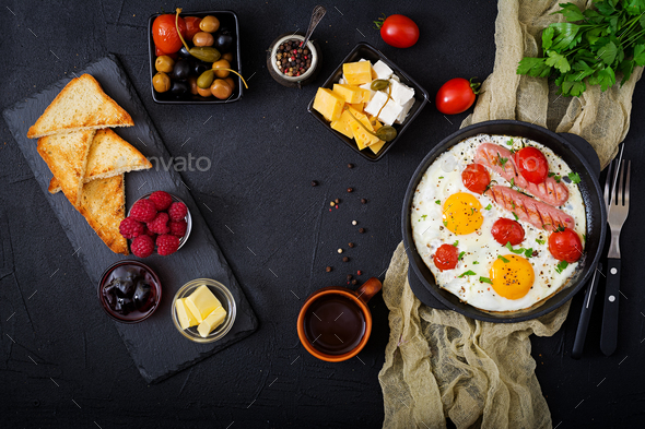 English breakfast - fried egg,  tomatoes and sausage. Top view. Flat lay - Stock Photo - Images
