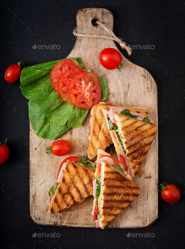 Club sandwich panini with ham, tomato, cheese and basil. Flat lay. Top view - Stock Photo - Images
