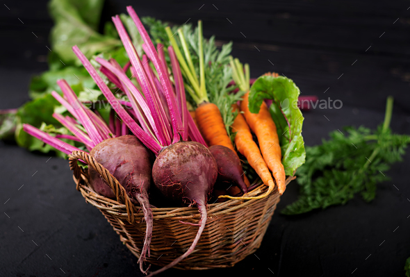 Young beetroot and carrots with a tops in a basket on a dark background. - Stock Photo - Images