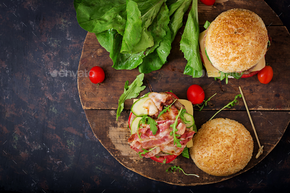 Big sandwich - hamburger burger with beef, cheese, tomato, cucumber and fried bacon - Stock Photo - Images