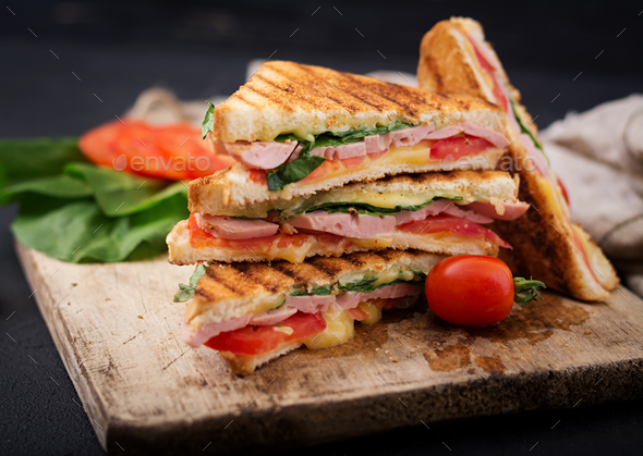 Club sandwich panini with ham, tomato, cheese and basil. - Stock Photo - Images
