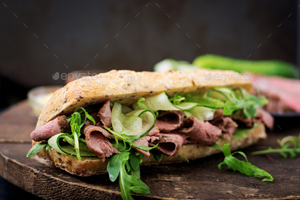 Sandwich of whole wheat bread with roast beef, cucumber and arugula - Stock Photo - Images