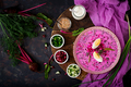 Cold beetroot (beet) soup on yogurt with egg, onion and cucumbers. Flat lay. Top view.