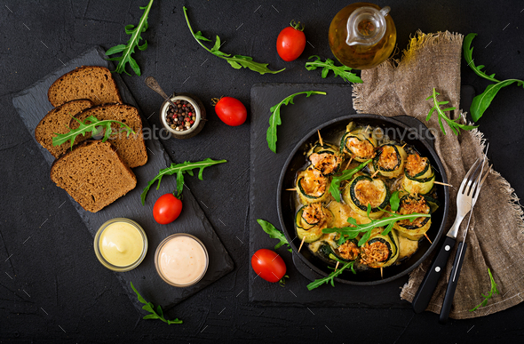 Baked zucchini rolls with cheese, carrot and chicken breast. Flat lay. Top view - Stock Photo - Images