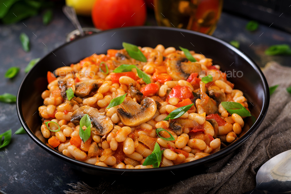 Stewed white beans with mushrooms and tomatoes with spicy sauce in a black bowl. - Stock Photo - Images