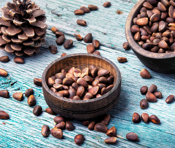 unpeeled cedar nut in mortar - Stock Photo - Images