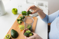 woman hand adding broccoli to measuring cup