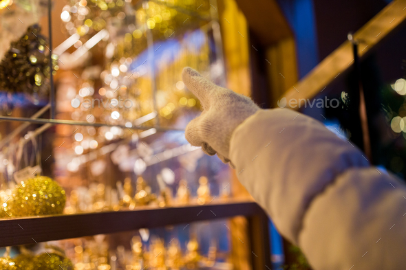 hand pointing at christmas toys behind shop window - Stock Photo - Images