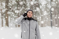 happy sports man with earphones in winter forest