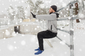 sports man doing squats at fence in winter