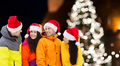 friends in santa hats and ski suits at christmas