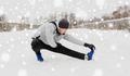man exercising and stretching leg on winter bridge