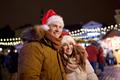 happy couple in santa hats at christmas market
