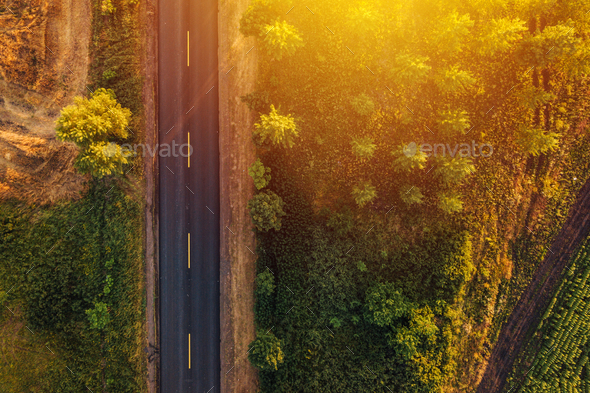 Empty road through countryside in sunset, aerial view drone pov - Stock Photo - Images