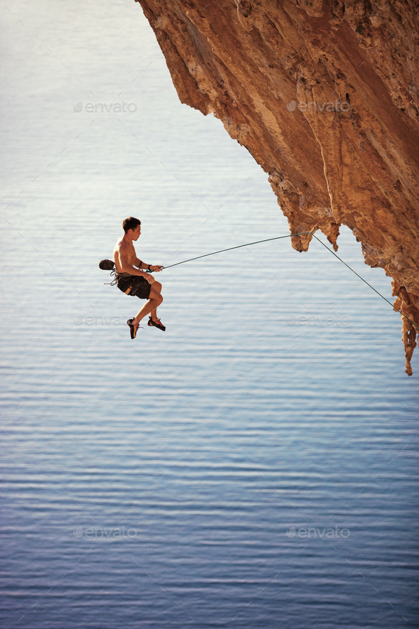 Rock climber falling of a cliff while lead climbing - Stock Photo - Images