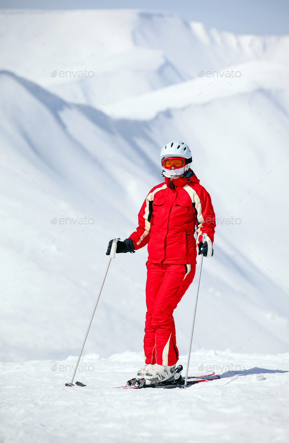 Female skier standing on mountain slope - Stock Photo - Images