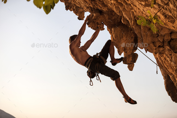 Rock climber against sky at sunset - Stock Photo - Images
