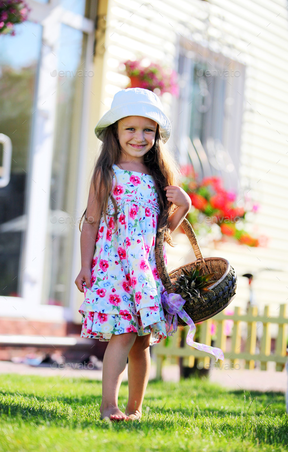 Cute four-year girl looking at camera outdoors - Stock Photo - Images