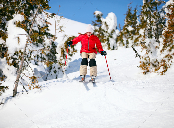 Young female skier about to jump on snowy slope - Stock Photo - Images