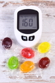 Glucose meter for measuring sugar level and colorful candies, reduction eating sweets concept