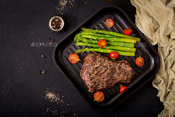 Juicy steak rare beef with spices on a wooden board and garnish of asparagus. Flat lay. Top view - Stock Photo - Images