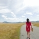 Girl Walking in a Field on the Way to the Mountains in a Red Dress - VideoHive Item for Sale
