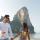 Couple Walking On Beach Holding Hands Talking Young Man And Woman Tourists On Vacation - VideoHive Item for Sale