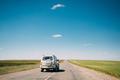 Gray SUV Car rides along Road In Spring Summer Fields Landscape