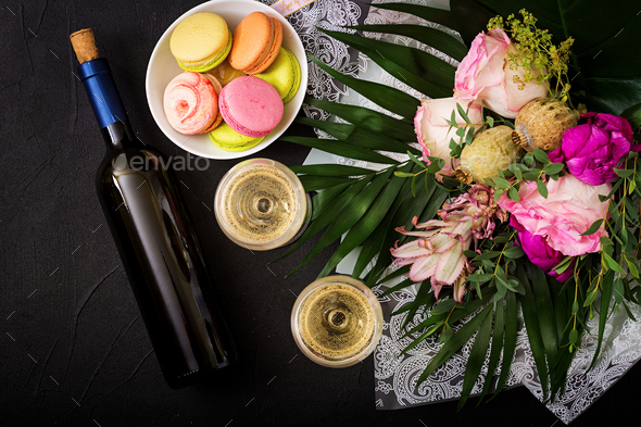 Bottle of dry white wine and a macaroon. Flat lay. Top view. - Stock Photo - Images