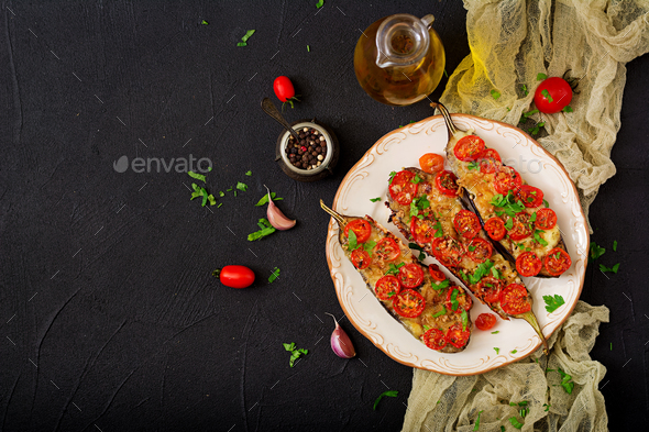 Baked eggplants with mozzarella and tomatoes with Italian herbs. Flat lay. Top view - Stock Photo - Images