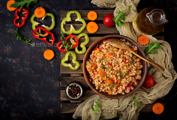 Vegetarian crumbly pearl barley porridge with vegetables  in a dark background. Flat lay. Top view - Stock Photo - Images