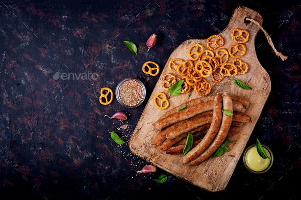 Pretzels and grilled sausages on dark background. Oktoberfest. Flat lay. Top view - Stock Photo - Images