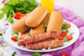Ingredients for hot dog with sausage. bacon, cucumber, tomato and red onion on white plate
