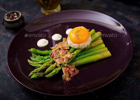 Young shoots of asparagus with ham and chicken egg yolk on toast - Stock Photo - Images