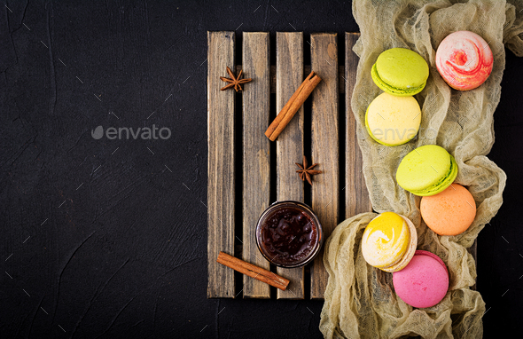Colorful macaroons and a  jar of honey on a wooden background. Flat lay. Top view - Stock Photo - Images
