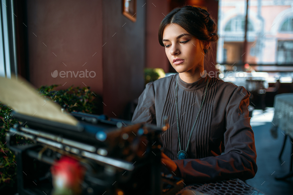 Serious lady prints on ancient typewriter - Stock Photo - Images