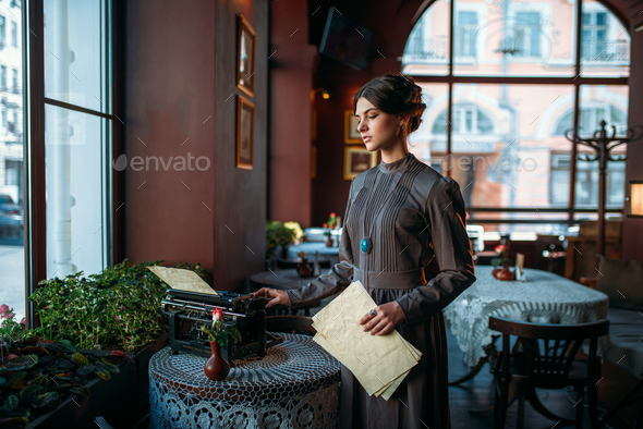 Serious dark hair lady stands near table - Stock Photo - Images