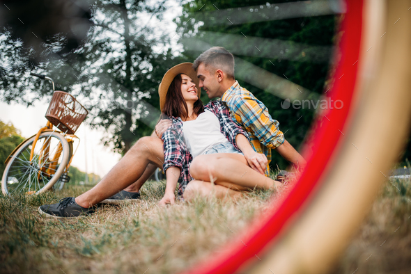 Love couple with vintage bikes sitting on grass - Stock Photo - Images