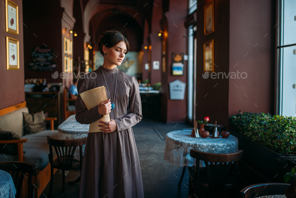 Young female person stands inside of cafe - Stock Photo - Images