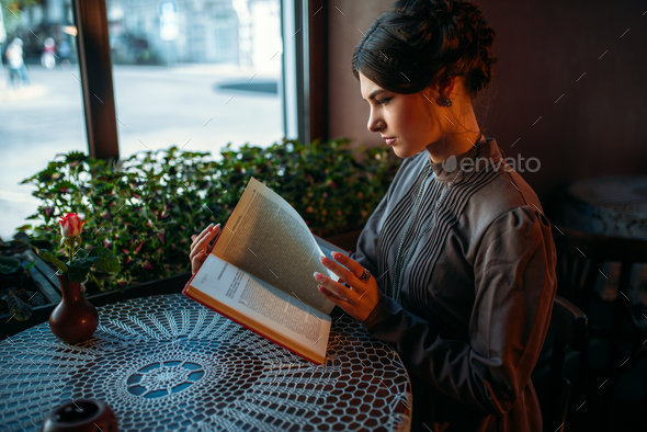 Portrait of lady in cafe reading book near window - Stock Photo - Images