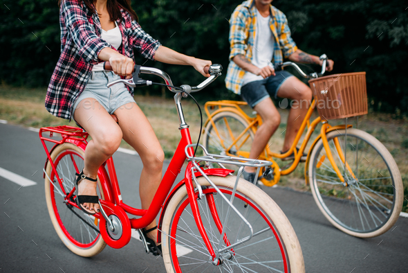 Male and female persons riding on retro bikes - Stock Photo - Images