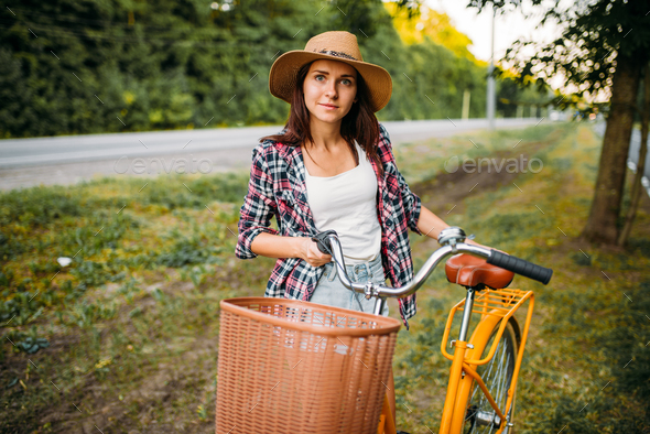Woman in hat against vintage bicycle with basket - Stock Photo - Images