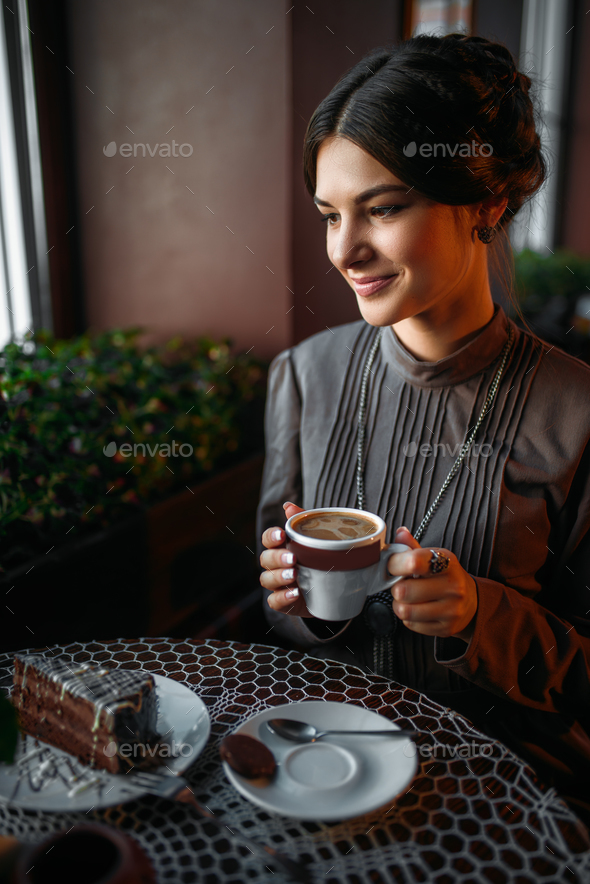 A young girl with a cup of coffee in retro cafe - Stock Photo - Images
