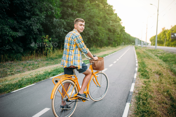 Young man on yellow vintage bicycle with basket - Stock Photo - Images