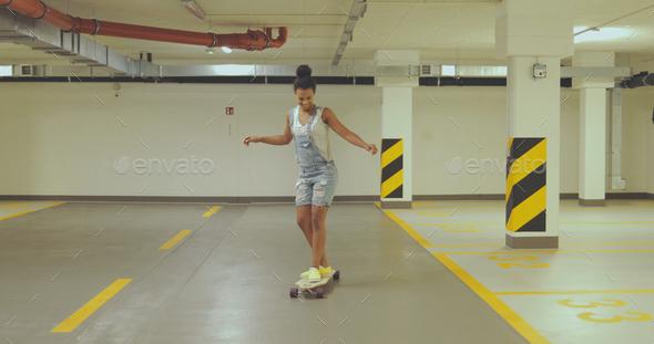 Girl skateboarding on parking - Stock Photo - Images
