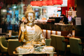 Statue Of Buddha Sitting In Lotus Position With Raised Right Arm