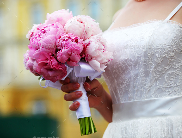 Closeup view of a bride holding bouquet of peonies - Stock Photo - Images